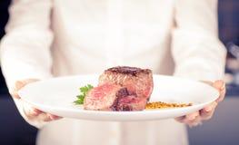 De chef-kok houdt een schotel Stock Afbeeldingen