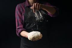 De chef-kok houdt het deeg en giet bloem op een donkere achtergrond Het concept voeding royalty-vrije stock foto