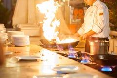 De chef-kok in de keuken van het restaurant op het fornuis met een pan, koks over hoge hitte stock afbeelding
