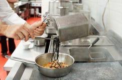 De chef-kok kookt deegwaren bij commerciële keuken Royalty-vrije Stock Foto's