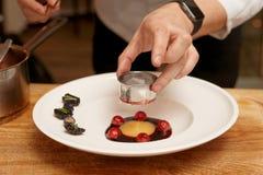 De chef-kok kookt gastronomische schotel Stock Fotografie