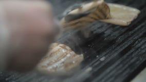 De chef-kok kookt pijlinktvis op een barbecuegrill stock video