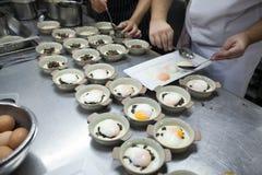 De chef-kok krijgt zacht-gekookte eieren op witte plaat gezet op ceramische kom Royalty-vrije Stock Fotografie