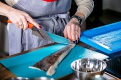 De chef-kok maakt vissen van schalen schoon Hoofdklasse in de keuken Het proces om te koken Stap voor stap leerprogramma Close-up royalty-vrije stock foto's
