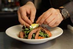 De chef-kok maakt voorgerecht met vlees Royalty-vrije Stock Afbeeldingen