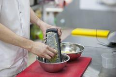 De chef-kok maalt de handen van de aardappelschef-kok ` s, hakbord, rasp stock foto's