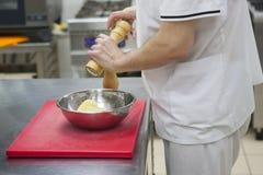 De chef-kok maalt de handen van de aardappelschef-kok ` s, hakbord, rasp royalty-vrije stock fotografie