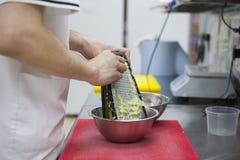 De chef-kok maalt de handen van de aardappelschef-kok ` s, hakbord, rasp stock foto
