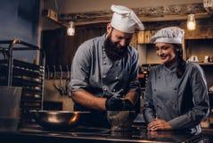 De chef-kok maalt sesamzaden in een mortier voor het koken van brood Chef-kok die zijn medewerker onderwijzen om het brood in bak stock foto