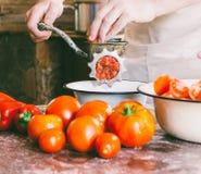 De chef-kok maalt stukken rijpe tomaten in een oude uitstekende handmolen om eigengemaakte saus, ketchup te maken stock fotografie