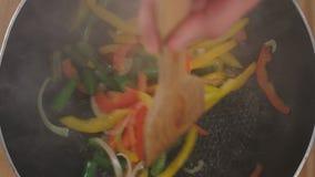 De chef-kok mengt de groenten in een pan stock videobeelden