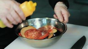 De chef-kok mengt ingrediënten van plantaardige salade in een kom Close-up van het bewegen van plantaardige salade met saus in ee stock videobeelden