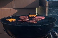 De chef-kok met het mes, die het hamburgerbrood voor de menigte snijden In het bijzonder lopen de sausen die op mayonaise worden  stock afbeelding