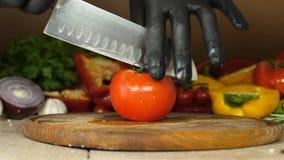 De chef-kok met zwarte handschoenen snijdt een sappige rode tomaat met druipende waterdruppeltjes op de twee helften op een houte stock video