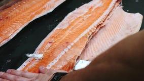 De chef-kok neemt beenderen van de zalmfilet, scherpe vissen op plakken voor het koken van sushi in 4k-resolutie in langzame moti stock videobeelden