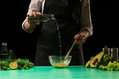 De chef-kok op een zwarte achtergrond maakt het koken van een groene detox smoothie Gezond, schoon voedsel, het voedselconcept va stock foto