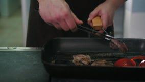 De chef-kok op keuken braadt vlees en groenten in een pan stock footage