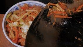 De chef-kok Puts Chinese Noodles met Groenten en het Vlees in een Kom, sluiten omhoog Geschoten stock footage