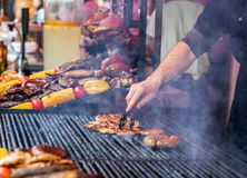 De chef-kok roostert perfect lapje vlees op gietijzerrooster royalty-vrije stock afbeelding