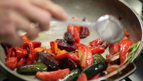 De chef-kok roostert verse groenten in een pan met stock video