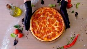 De chef-kok in rubberhandschoenen neemt pizzasalami op een houten Raad van de lijst Het proces van spijkers stock videobeelden