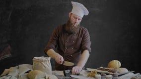 De chef-kok scherpt het mes en controleert de scherpte dan de glimlachen en bekijkt de camera stock videobeelden