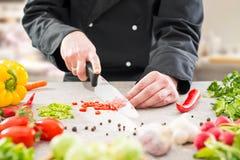 De chef-kok snijdende groenten royalty-vrije stock foto