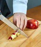 De chef-kok snijdt een rode appel voor het koken van overwogen wijn een volledige inzameling van culinaire recepten Stock Fotografie