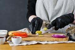 De chef-kok snijdt groenten in het zuur r Eigengemaakt hamburgerrecept Keuken, zijaanzicht, ruimte voor tekst stock afbeeldingen