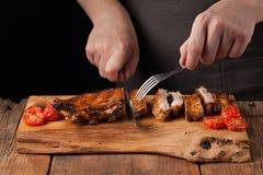 De chef-kok snijdt het met een scherp mes klaar om varkensvleesribben te eten, liggend op een oude houten lijst Een mens bereidt  Royalty-vrije Stock Fotografie