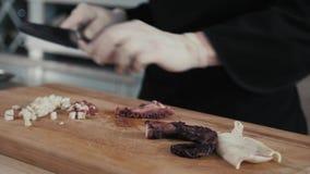 De chef-kok snijdt octopus klaar voor dicht omhoog het eten, zeevruchtenrestaurant stock video