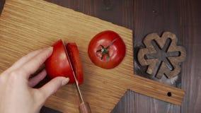 De chef-kok snijdt de tomaat door scherp staalmes op de houten raad, die de salade, het maken koken van vegetarische maaltijd, ge stock footage