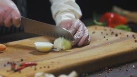 De chef-kok snijdt ui Uien als ingrediënt voor het maken van soep of een andere schotel Hoogste menings Langzame motie stock videobeelden