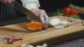 De chef-kok snijdt wortel wortel als ingrediënt voor het maken van soep of een andere schotel Hoogste menings Langzame motie stock videobeelden