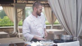 De chef-kok spreekt aan de bezoekers van het restaurant die yul kiezen doe voor een culinaire show stock video