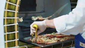 De chef-kok trekt zich van rode krabben van de ovengrill terug Heerlijke tentakels van de rode krab stock footage