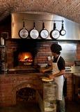 De Chef-kok van de pizza zette de pizza binnen de Houten Oven stock foto