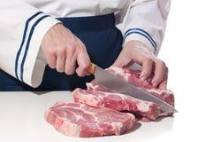 De chef-kok van de vrouw snijdt het vlees. Royalty-vrije Stock Fotografie