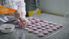 De chef-kok van het chef-kokgebakje gekleed in wit kostuum en een transparante handschoen smeert een dikke ganache op half purper stock videobeelden