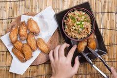 De chef-kok verfraaide gebraden kippenvleugels die met gebraden gerechtrijst worden gediend Royalty-vrije Stock Fotografie