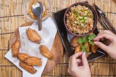 De chef-kok verfraaide gebraden kippenvleugels die met gebraden gerechtrijst worden gediend Stock Afbeeldingen