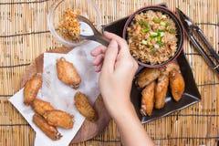 De chef-kok verfraaide gebraden kippenvleugels die met gebraden gerechtrijst worden gediend Stock Fotografie