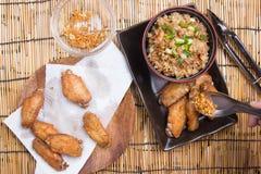 De chef-kok verfraaide gebraden kippenvleugels die met gebraden gerechtrijst worden gediend Royalty-vrije Stock Foto's