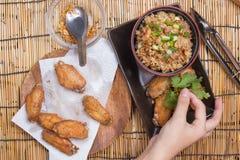 De chef-kok verfraaide gebraden kippenvleugels die met gebraden gerechtrijst worden gediend Stock Foto