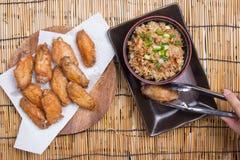 De chef-kok verfraaide gebraden kippenvleugels die met gebraden gerechtrijst worden gediend Royalty-vrije Stock Afbeelding