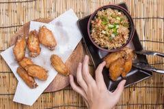 De chef-kok verfraaide gebraden kippenvleugels die met gebraden gerechtrijst worden gediend Stock Afbeelding