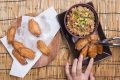 De chef-kok verfraaide gebraden kippenvleugels die met gebraden gerechtrijst worden gediend Stock Foto's