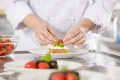 De chef-kok verfraait dessertcake met aardbei Stock Foto