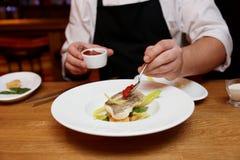 De chef-kok verfraait een visschotel Stock Afbeeldingen