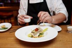De chef-kok verfraait een visschotel Stock Foto